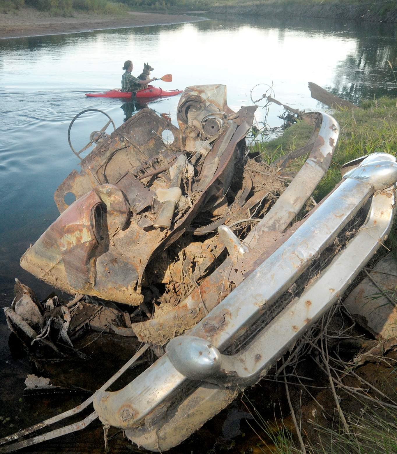 Junk cars emerge from river\'s banks