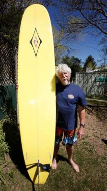 Surfing pioneer Jim Graham with his long board at his Durango home.