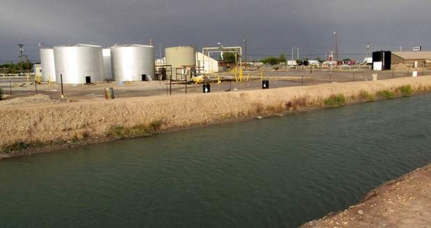Empty water tanks sit at the edge of a brine well operation, shown at right of tanks, as a major irrigation canal flows by in Carlsbad, N.M. Almost half of Carlsbad school bus routes travel over the well, on a busy road that borders a giant, underground cavern that resulted from years of manufacturing brine for the oil and gas industry. It's been nearly nine years since state officials first sounded the alarm about a potential collapse, but experts say could happen at any time.