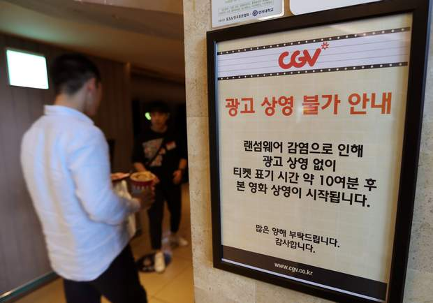 "A customer walks by the notice about ""ransomware"" at CGV theater in Seoul, South Korea, on Monday. The letters read ""Due to ransomware affection, we are unable to screen advertisement. The movie is going to start 10 minutes after the ticket time."""