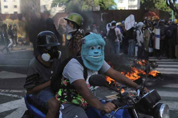 An anti-government protester wearing a mask depicting the Monster Inc. character Sulley drives a motorbike through a barricade set up by fellow protesters, in Caracas, Venezuela, Thursday, May 18, 2017. The protest in Caracas comes after a tumultuous 24 hours of looting and protests in the western state of Tachira that led the government to send in troop reinforcements. More than 40 people have been killed in almost two months of unrest in Venezuela. (AP Photo/Fernando Llano)