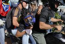 An anti-government protester is taken away on a motorcycle by other demonstrators after injuring his leg during clashes with security forces in Caracas, Venezuela, Thursday, May 18, 2017. The protest in Caracas comes after a tumultuous 24 hours of looting and protests in the western state of Tachira that led the government to send in troop reinforcements, and after almost two months of unrest nationwide in which more than 40 people have been killed. (AP Photo/Ariana Cubillos)