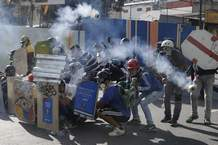 Anti-government protesters shield themselves from tear gas as security forces try to disperse them, in Caracas, Venezuela, Thursday, May 18, 2017. The protest in Caracas comes after a tumultuous 24 hours of looting and protests in the western state of Tachira that led the government to send in troop reinforcements, and after almost two months of unrest nationwide in which more than 40 people have been killed. (AP Photo/Ariana Cubillos)