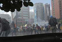Anti-government protesters shield themselves from sprays of water as security forces try to disperse them, in Caracas, Venezuela, Thursday, May 18, 2017. The protest in Caracas comes after a tumultuous 24 hours of looting and protests in the western state of Tachira that led the government to send in troop reinforcements. More than 40 people have been killed in almost two months of unrest in Venezuela. (AP Photo/Fernando Llano)