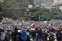 Anti-government protesters make their way to the Interior Ministry, before clashing with National Guards who blocked them in Caracas, Venezuela, Thursday, May 18, 2017. The protest in Caracas comes after a tumultuous 24 hours of looting and protests in the western state of Tachira that led the government to send in troop reinforcements, and after almost two months of unrest nationwide in which more than 40 people have been killed. (AP Photo/Ariana Cubillos)