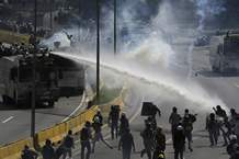 A water canon sprays government protesters trying to reach the Interior Ministry, in Caracas, Venezuela, Thursday, May 18, 2017. The protest in Caracas comes after a tumultuous 24 hours of looting and protests in the western state of Tachira that led the government to send in troop reinforcements, and after almost two months of unrest nationwide in which more than 40 people have been killed. (AP Photo/Fernando Llano)