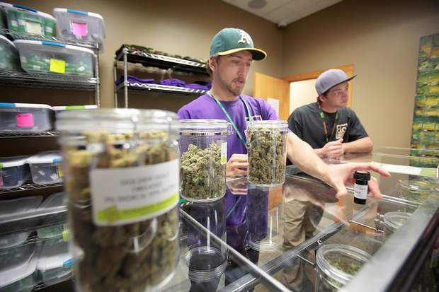 Tanner Waldron, left, and Nick Noto of Durango Organics help customers in September 2014 with their selections during the first day of retail marijuana sales in Durango.