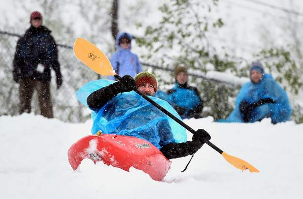 Justin Shannon, of Chico, California, uses a kayak to sled down the hill Thursday at Tantra Park in Boulder.