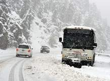 An RTD bus is stranded along Colorado Highway 119 at Boulder Falls Thursday during a steady snow in Boulder canyon. A rare May snow dump across Colorado has prompted some emergency warming shelters to re-open after being closed for the season.