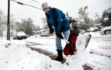 Susan Sullivan, of Boulder, shovels the sidewalk in front of her house on Emerson Street in the spring snowstorm Thursday in Boulder.