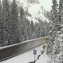 A webcam image shows a wet road surface and snow along the shoulders Thursday morning on Red Mountain Pass. A spring storm is expected to linger through Friday in the San Juan Mountains.