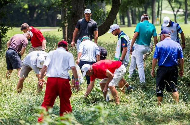 Brooks Koepka, top center, watches as spectators and officials looks for his ball in the rough on the ninth hole during the first round of the Byron Nelson PGA golf tournament at TPC Four Seasons Resort in Irving, Texas, Thursday, May 18, 2017. (Ashley Landis/The Dallas Morning News via AP)