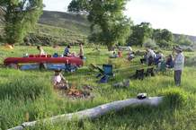 "River trips create river time where participants ""go with the flow,"" getting up at sunrise and heading to their tents at full dark. Two canoes become a river kitchen with food laid out on one canoe and dish washing on the other."