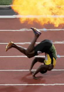 Fireworks for the winner goes off as Jamaica's Usain Bolt falls after suffering an injury, during the men's 4x100-meter final at the World Athletics Championships in London Saturday, Aug. 12, 2017. (AP Photo/Frank Augstein)