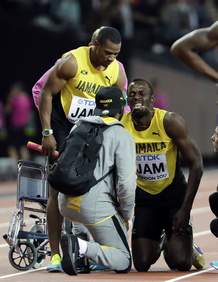 Jamaica's Usain Bolt, second right, receives treatment after he pulled up injured in the final of the Men's 4x100m relay during the World Athletics Championships in London Saturday, Aug. 12, 2017. (AP Photo/David J. Phillip)