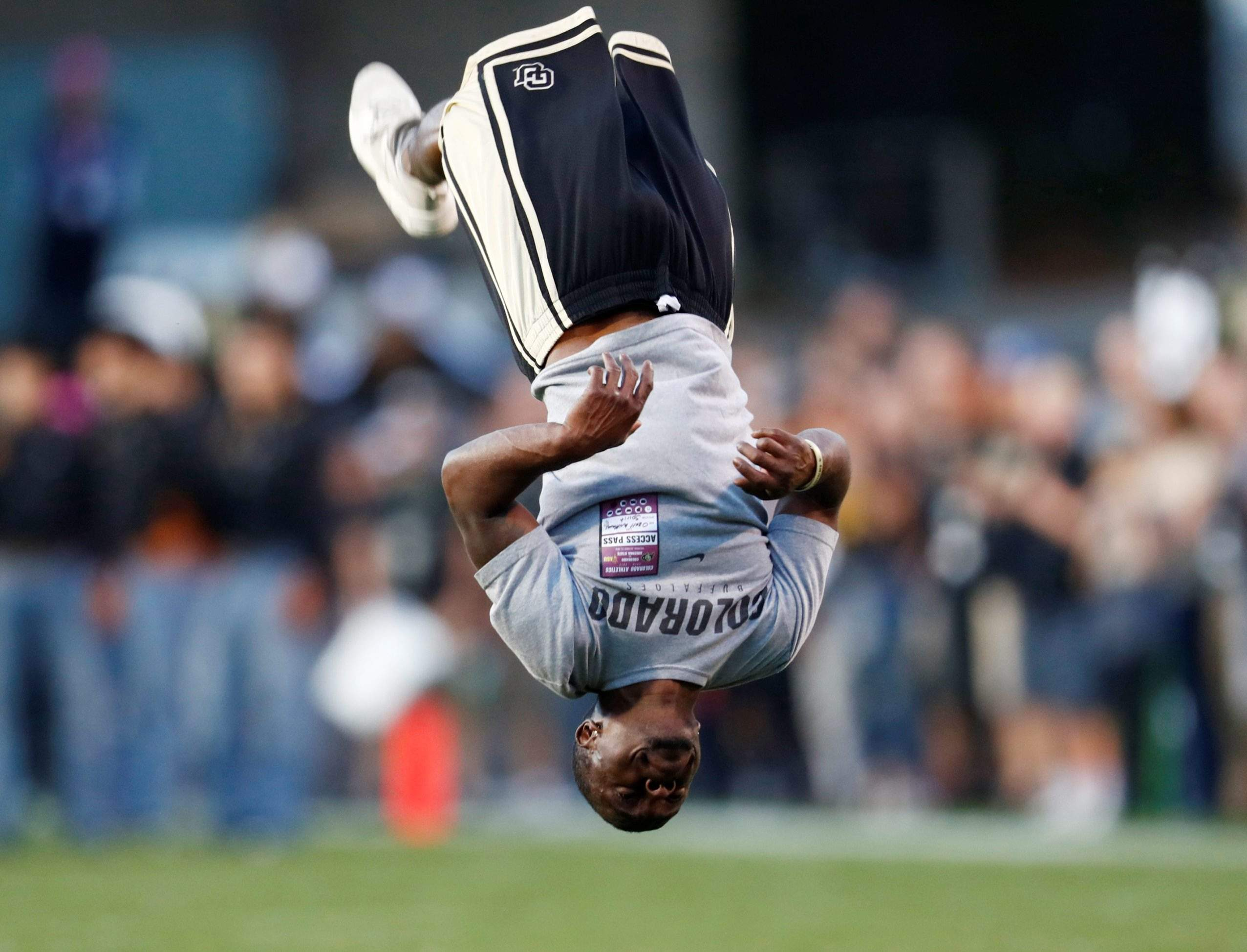 Ozell Williams performs a somersault as part of pre-game ceremonies before  Colorado hosts Arizona State in the first half of an NCAA college football  game ...