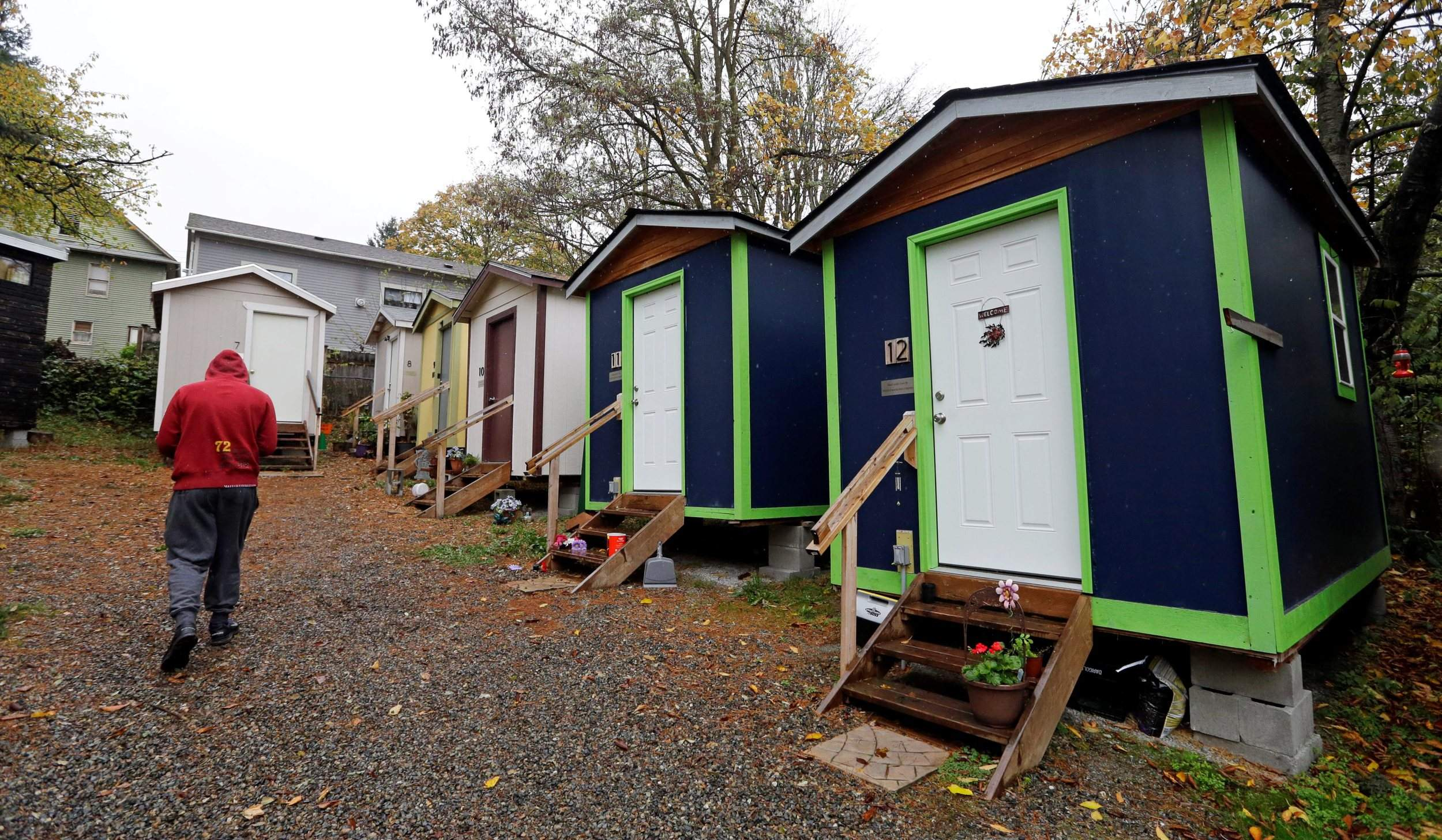 tiny houses for homeless. A Resident Walks Past Row Of Tiny Houses At Homeless Encampment In Seattle Where Full-size Homes Stand Behind On Nov. 9. For