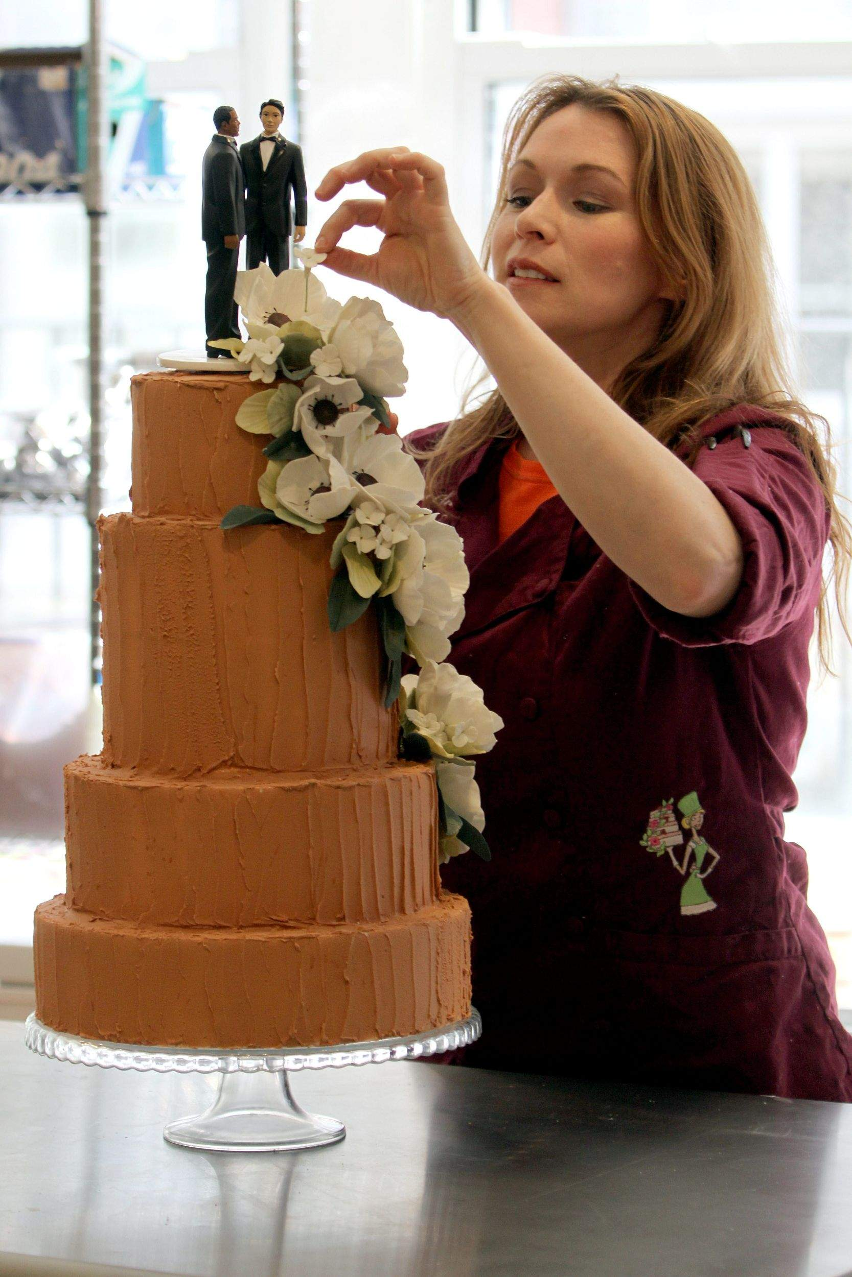 Amy DeGiulio Owner Of Sugar Flower Cake Shop Decorates A White With Strawberry Buttercream Filling And Chocolate Icing In New York