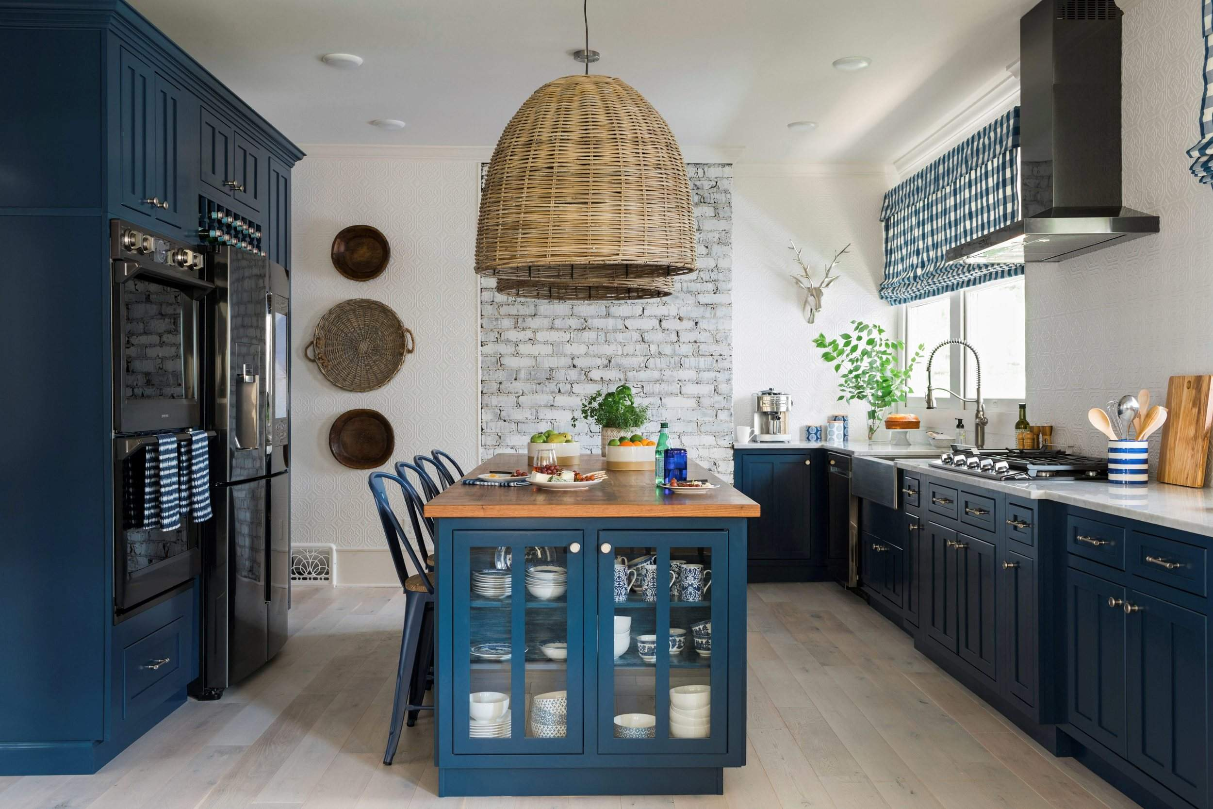 A kitchen designed by brian patrick flynn features a l shaped perimeter design with lower cabinets painted a rich shade of navy blue a style choice that