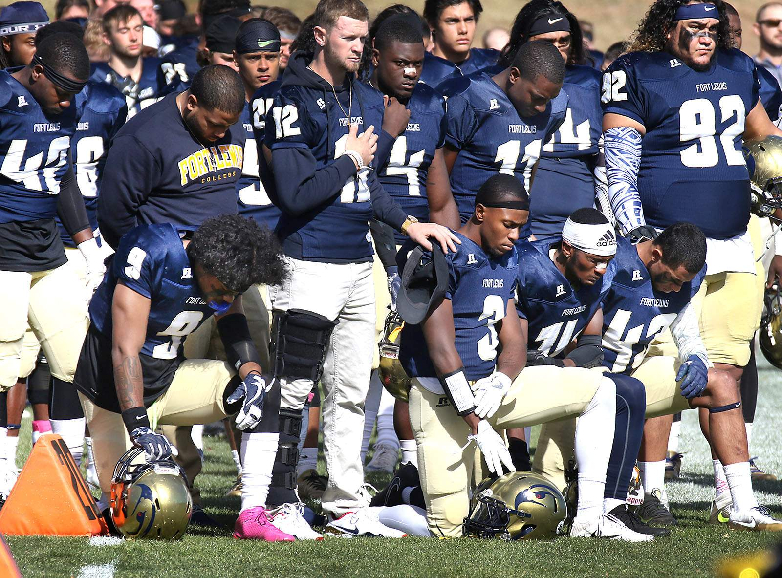 Four Fort Lewis College football players kneel during ...