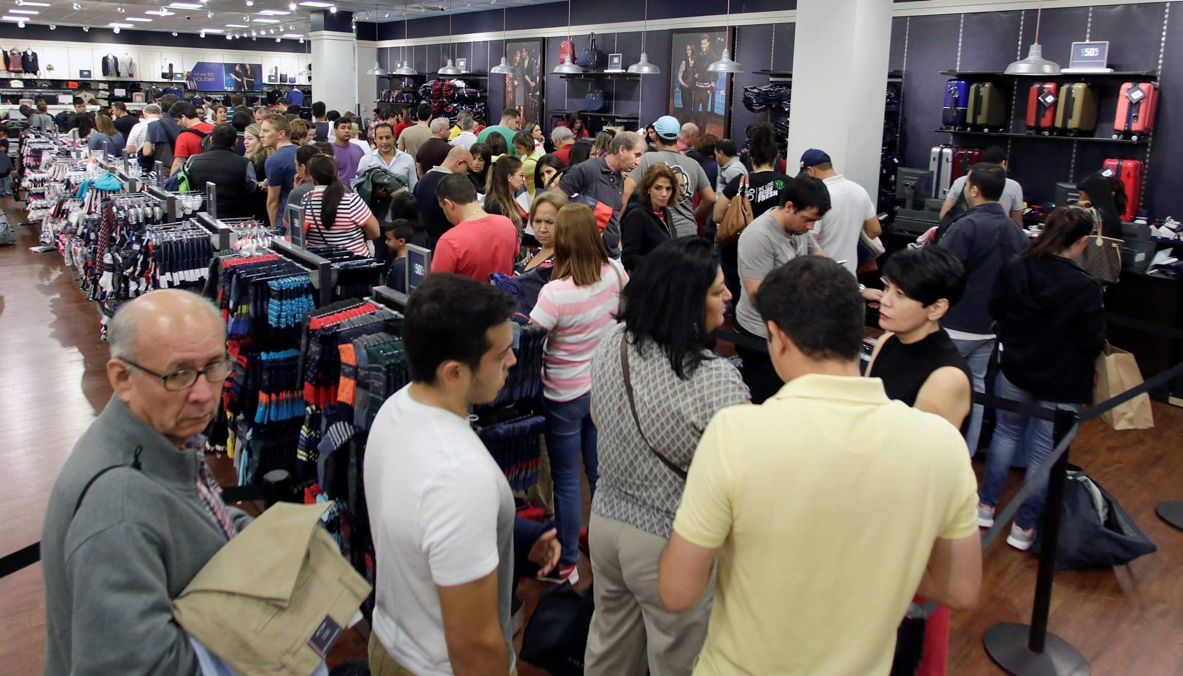 c5984155 Shoppers stand in line to pay at a Tommy Hilfiger store on Black Friday  last year in Miami. Fewer customers say they will shop on Black Friday  compared with ...