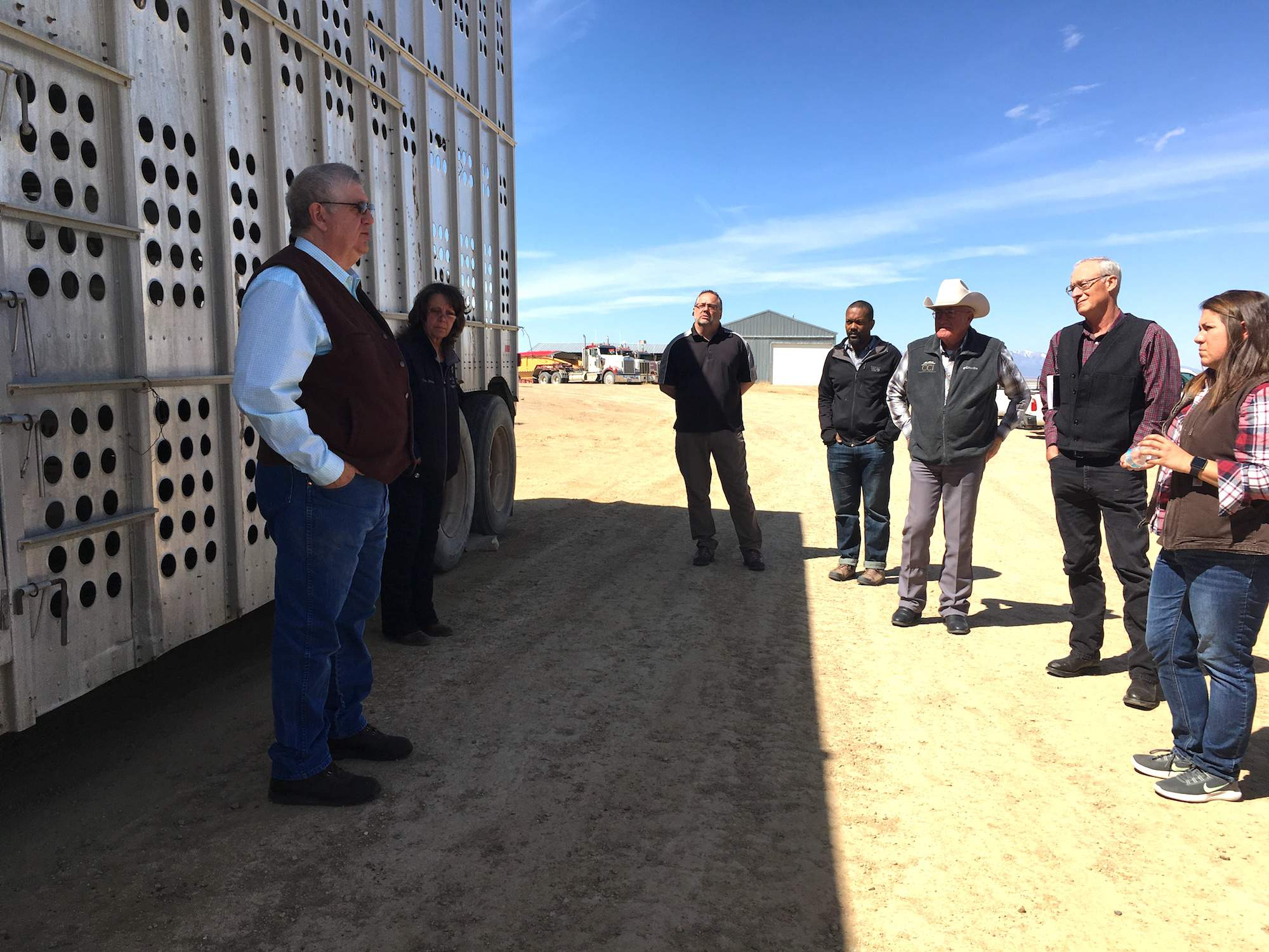 Extension educators and emergency managers discuss next to a livestock trailer