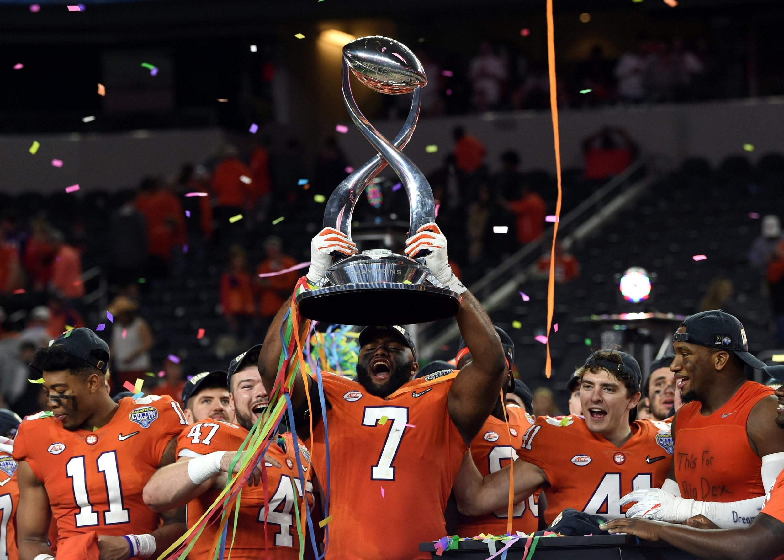 Clemson defensive end Austin Bryant holds up the trophy as the team  celebrates their 30-3 win against Notre Dame in the Cotton Bowl semifinal playoff  game ... dd501a0a4