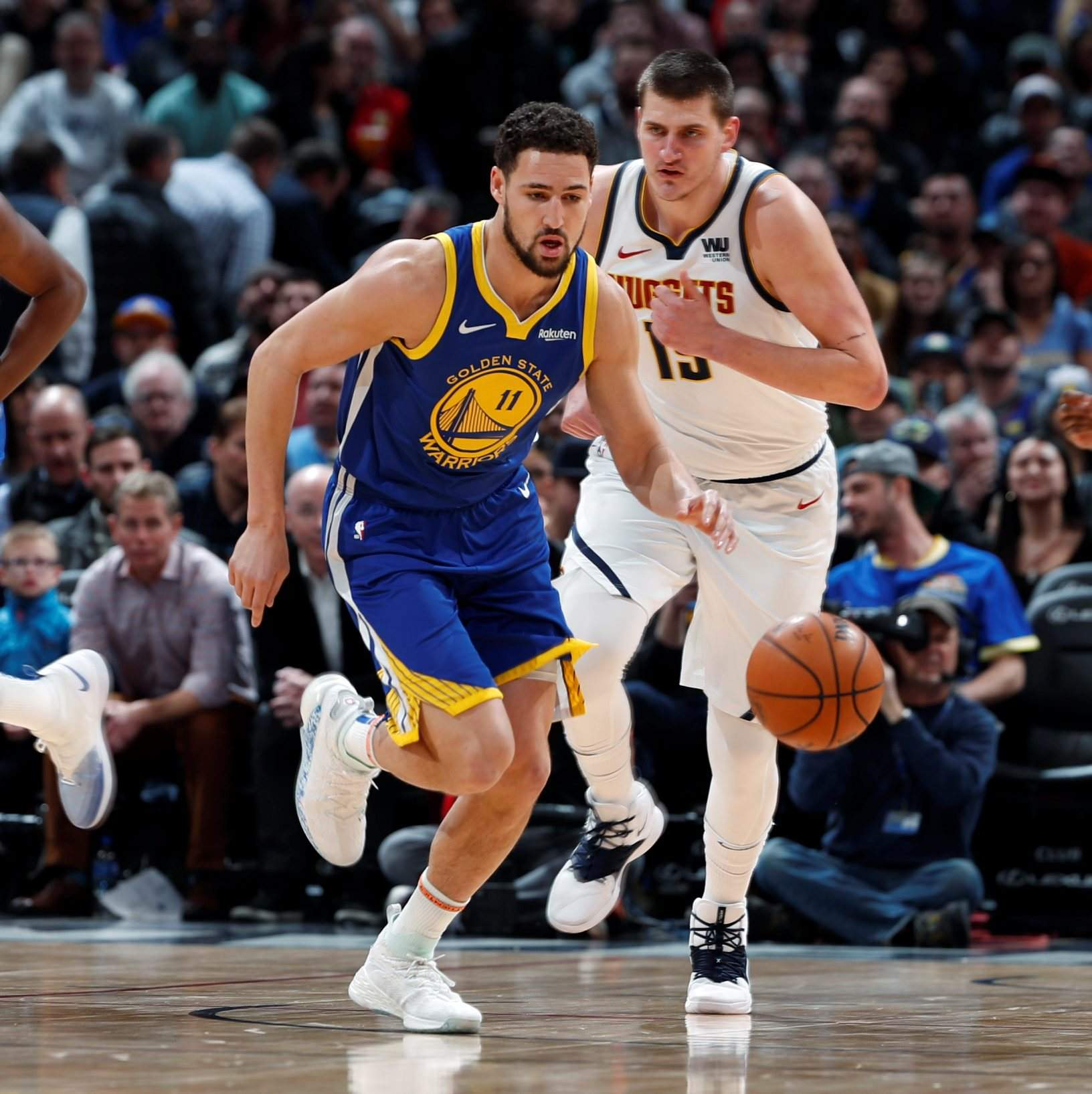 ad03bff99576 Golden State Warriors guard Klay Thompson tracks down a loose ball as  Denver Nuggets center Nikola Jokic follows in the first half Tuesday in  Denver.