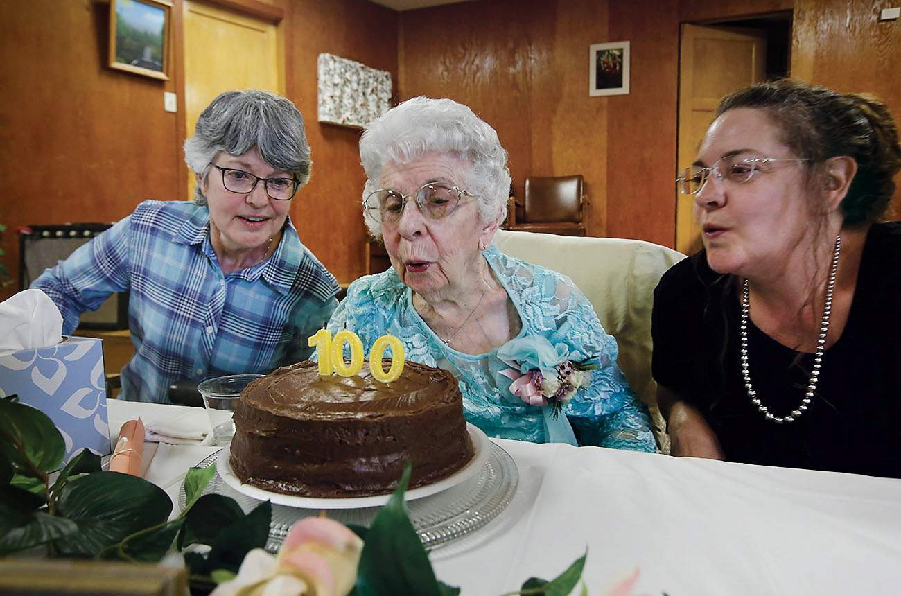 Mildred Hubbs Gets A Little Assistance From Her Granddaughters LaJuan Left And Jeanene Largent As She Blows Out Candles On Birthday Cake During